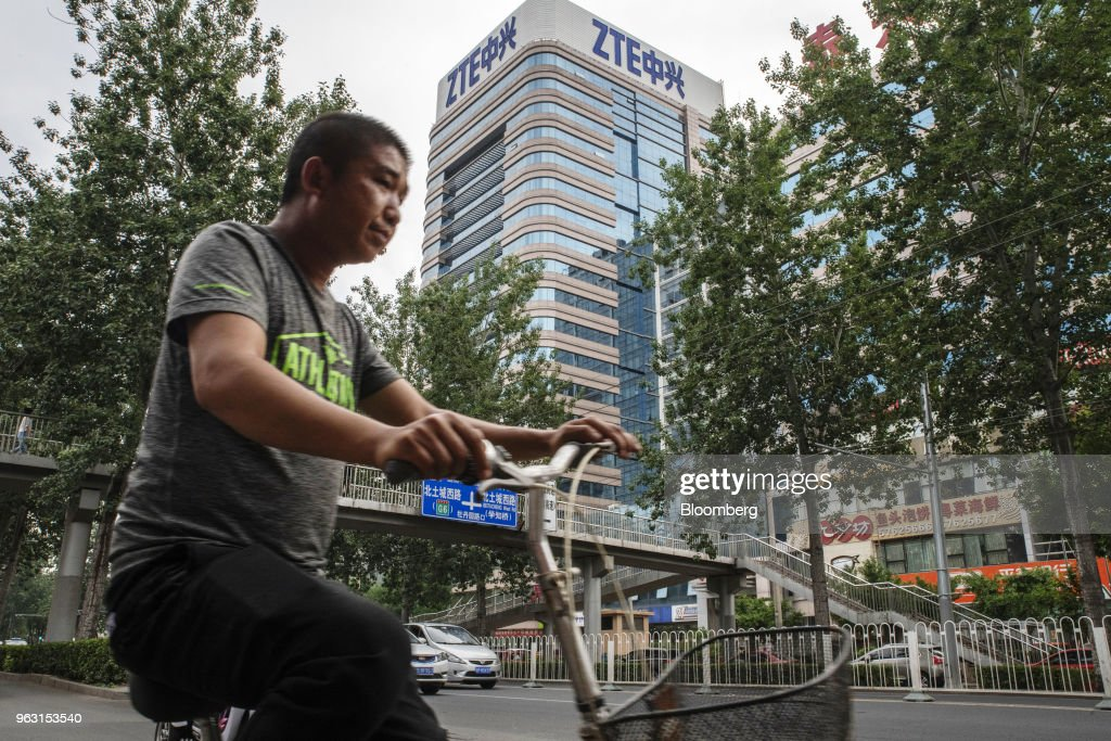 A man rides a bicycle past a ZTE Corp. building in Beijing, China, on Thursday, May 24, 2018. PresidentDonald Trumpsaid the U.S. would allow Chinese telecommunications-equipment maker ZTE Corp. to remain in business after paying a $1.3 billion fine, changing its management and board and providing 'high-level security guarantees.' Photographer: Gilles Sabrie/Bloomberg via Getty Images