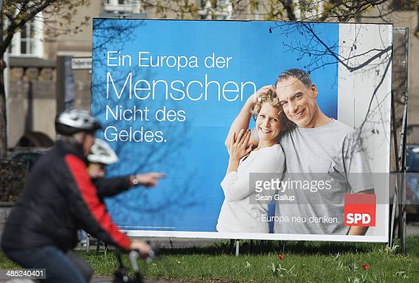 A man rides a bicycle past an election campaign poster of the German Social Democrats for European Union parliamentary elections that reads 'A Europe...