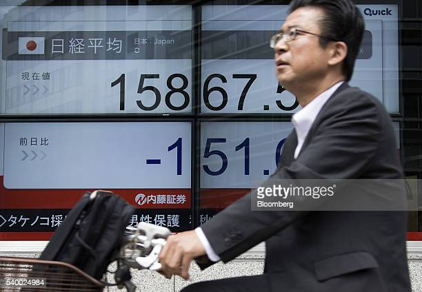 A man rides a bicycle past an electronic stock board displaying the Nikkei Stock Average outside a securities firm in Tokyo Japan on Tuesday June 14...