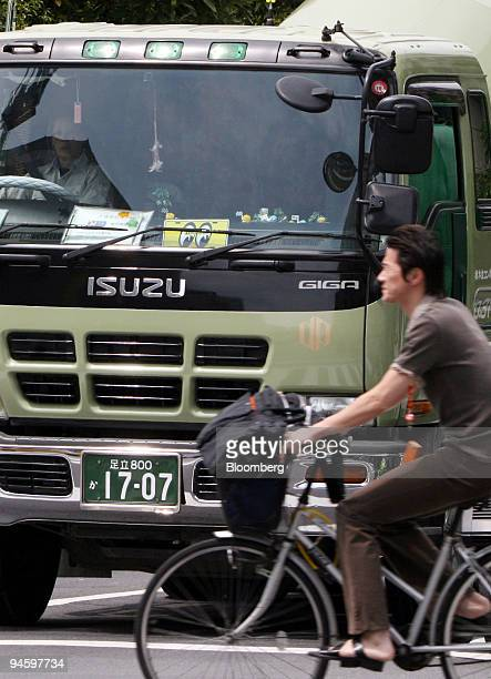 A man rides a bicycle past an Isuzu Motors Ltd Giga commercial truck in Tokyo Japan on Monday May 14 2007 Isuzu Motors Ltd Japan's biggest maker of...