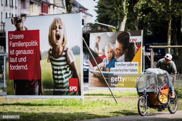 A man rides a bicycle past election campaign billboards of the German Social Democrats and the German Christian Democrats on August 24 2017 in...
