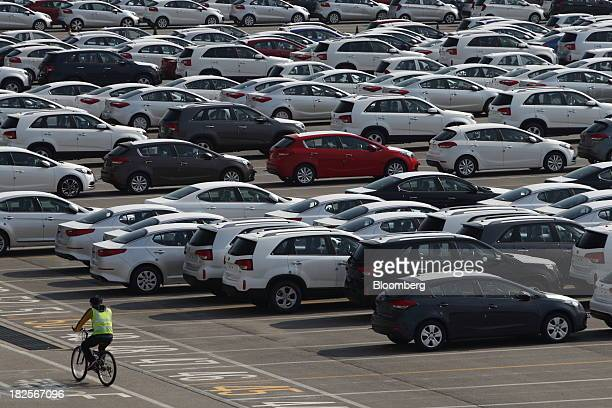 A man rides a bicycle past Kia Motors Corp vehicles bound for export at the port of Pyeongtaek in Pyeongtaek South Korea on Monday Sept 30 2013 South...