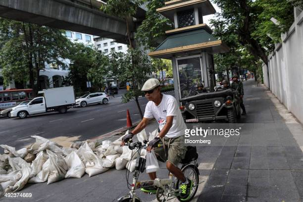 Man rides a bicycle past Royal Thai Army soldiers stationed near luxury hotels on Ratchadamri Road in central Bangkok, Thailand, on Tuesday, May 20,...