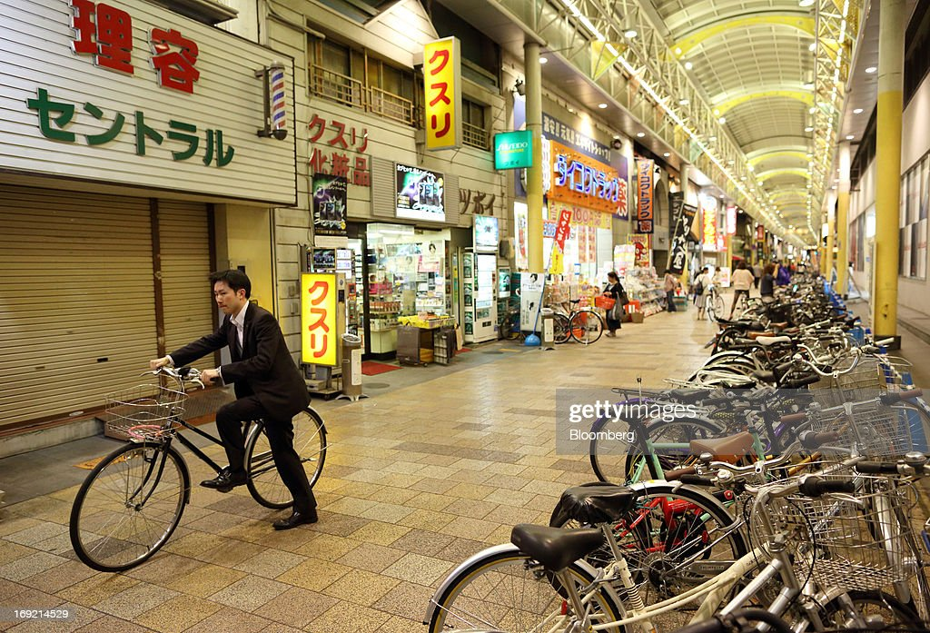 A man rides a bicycle past stores on a shopping street in Okayama, Japan, on Monday, May 20, 2013. The Bank of Japan, forecast to maintain plans for expanded monetary easing at a meeting ending on May 22, is targeting 2 percent inflation in two years after more than 10 years of entrenched deflation. Photographer: Tomohiro Ohsumi/Bloomberg via Getty Images