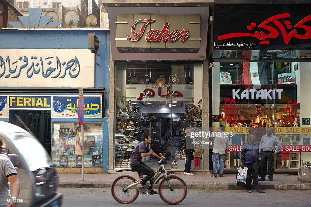 A man rides a bicycle past stores on a street in Cairo, Egypt, on Friday, Aug. 7, 2015. The Suez canal extension and other construction projects have boosted the economy, which grew above 4 percent in the nine months to March for the first time since 2010. Photographer: Shawn Baldwin/Bloomberg via Getty Images