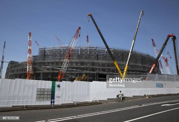 A man rides a bicycle past the construction site of the New National Stadium a venue for 2020 Summer Olympics and Paralympics in Tokyo Japan on...