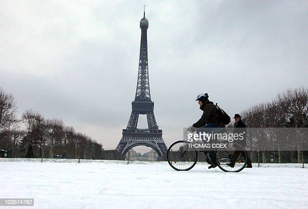 A man rides a bicycle past the Eiffel Tower in Paris under the snow on January 13 2010 A snow and sleet storm forced French authorities to ban travel...