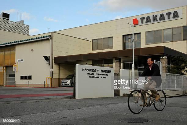 A man rides a bicycle past the entrance to Takata Corp's Nagahama plant in Nagahama Shiga Japan on Friday Nov 25 2016 Takata's selection of a bidder...