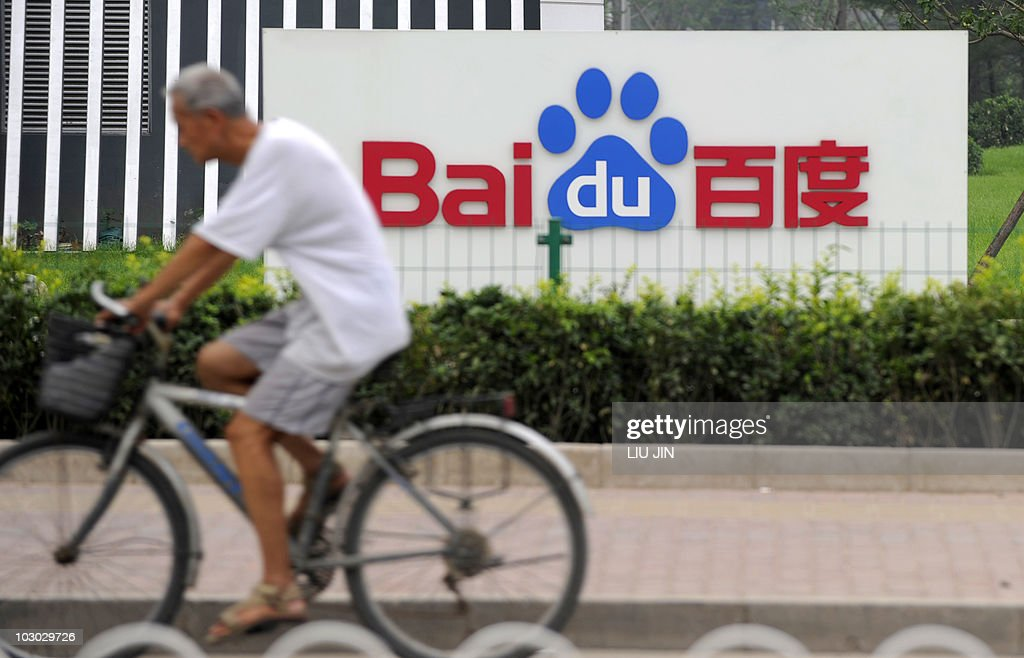 A man rides a bicycle past the logo of B : News Photo