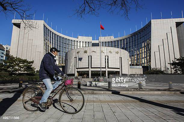 A man rides a bicycle past the People's Bank Of China headquarters in Beijing China on Wednesday Dec 2 2015 China's great rebalancing the longsought...