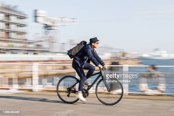 a man rides a bicycle to work in the town of bayside in the morning - bicycle stock pictures, royalty-free photos & images