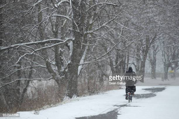 A man rides a bicycle under snow in Tiergarten park in the city center on March 20 2018 in Berlin Germany Snow is falling across Germany and weather...