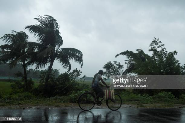 TOPSHOT A man rides a bicycle under the rain ahead of the expected landfall of cyclone Amphan in Midnapore West Bengal on May 20 2020 India and...