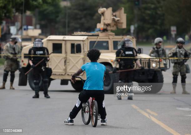 A man rides a bicycle up to a law enforcement checkpoint after the city endured a night of protests and violence on May 29 2020 in Minneapolis...