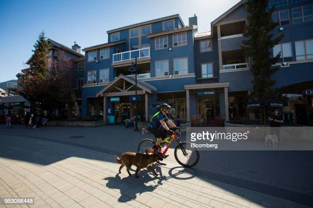 A man rides a bicycle with his dog through Village North in Whistler British Columbia Canada on Friday April 27 2018 The cost of a typical home in...