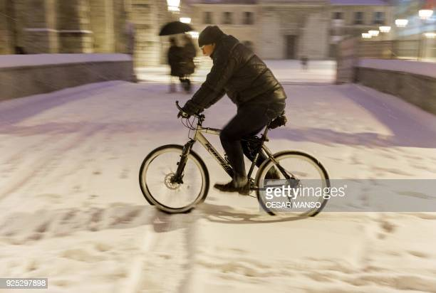A man rides a bicyle in the snow after a heavy snowfall in Burgos northern Spain on February 28 2018 School was cancelled across swathes of Europe as...