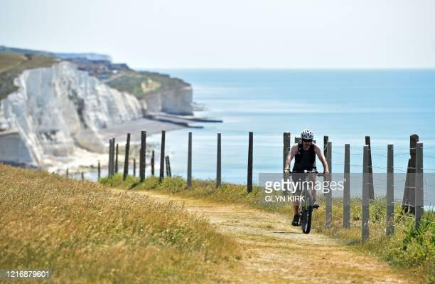 Man rides a bike along the coastal path from Saltdean towards Rottingdean near Brighton on the south coast of England on June 2, 2020 following a...