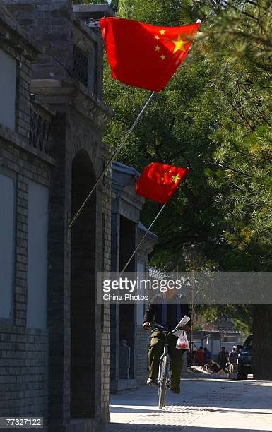 """Man rides a bike in a """"Hutong"""" alleyway decorated by Chinese national flags to mark the opening of the 17th CPC National Congress on October 15, 2007..."""