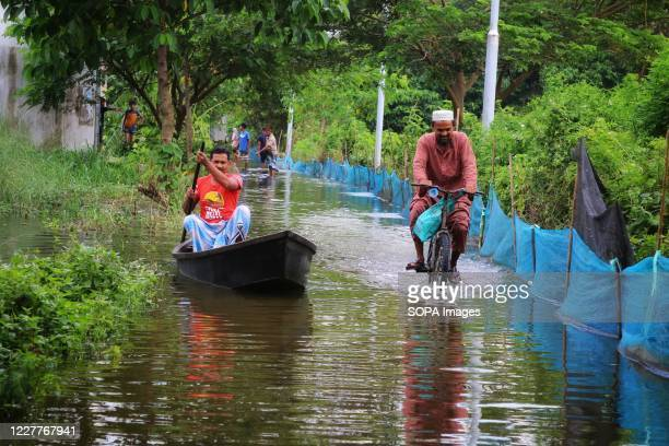 A man rides a bike on a submerged road alongside a boat at Demra area in Dhaka As many as 20 districts including the latest additions Chandpur...