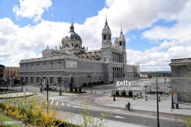 A man rides a bike on an empty street in front of the Almudena cathedral in Madrid on April 1 during a national lockdown to prevent the spread of the...