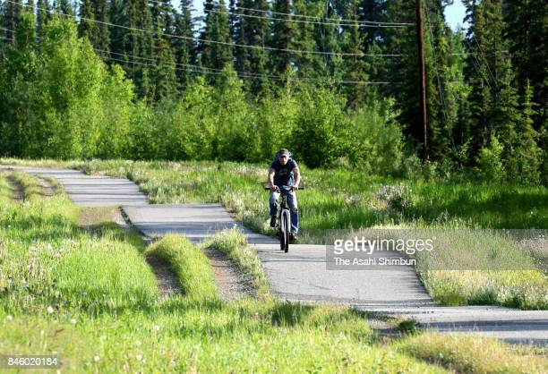 A man rides a bike on the undulating road as permafrost soil under topsoil had melted on June 18 2017 in Fairbanks Alaska United States In April 2017...