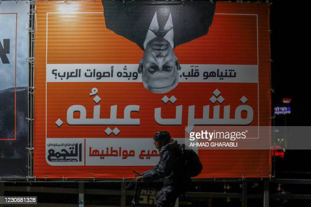 """Man rides a bike past a campaign billboard for the Balad Party, part of the joint Arab list, which reads in Arabic """"Now Netanyahu turned around,..."""