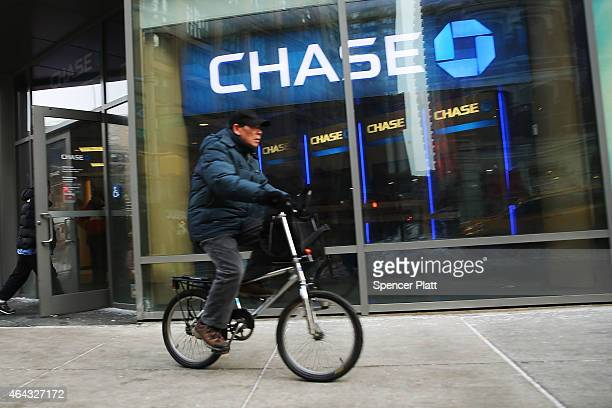 A man rides a bike past a Chase bank branch in Manhattan on February 24 2015 in New York City JPMorgan Chase announced today that they plan to close...
