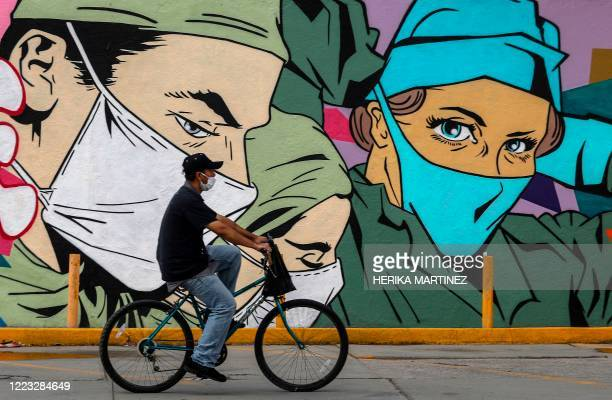 """Man rides a bike past a coronavirus-related mural by urban artists Mick Martinez and """"Were Torres"""" in Ciudad Juarez, Chihuahua state, Mexico, on June..."""