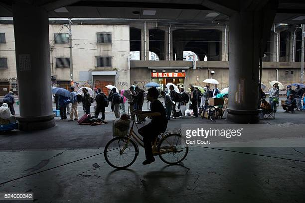 A man rides a bike past homeless people queueing to access a shelter in the slum area of Kamagasaki on April 23 2016 in Osaka Japan Kamagasaki a...