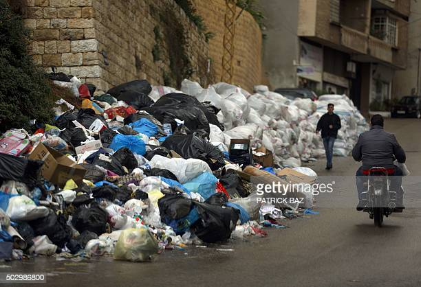 A man rides a bike past rubbish piled up on the street in Jdeideh northeast of Beirut on December 31 2015 AFP PHOTO / PATRICK BAZ / AFP / PATRICK BAZ