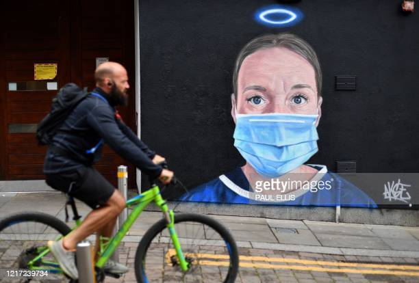 A man rides a bike past street art graffiti by the artist @akse_p19 depicting a nurse in scrubs and a face mask but with an Angel's halo above her...