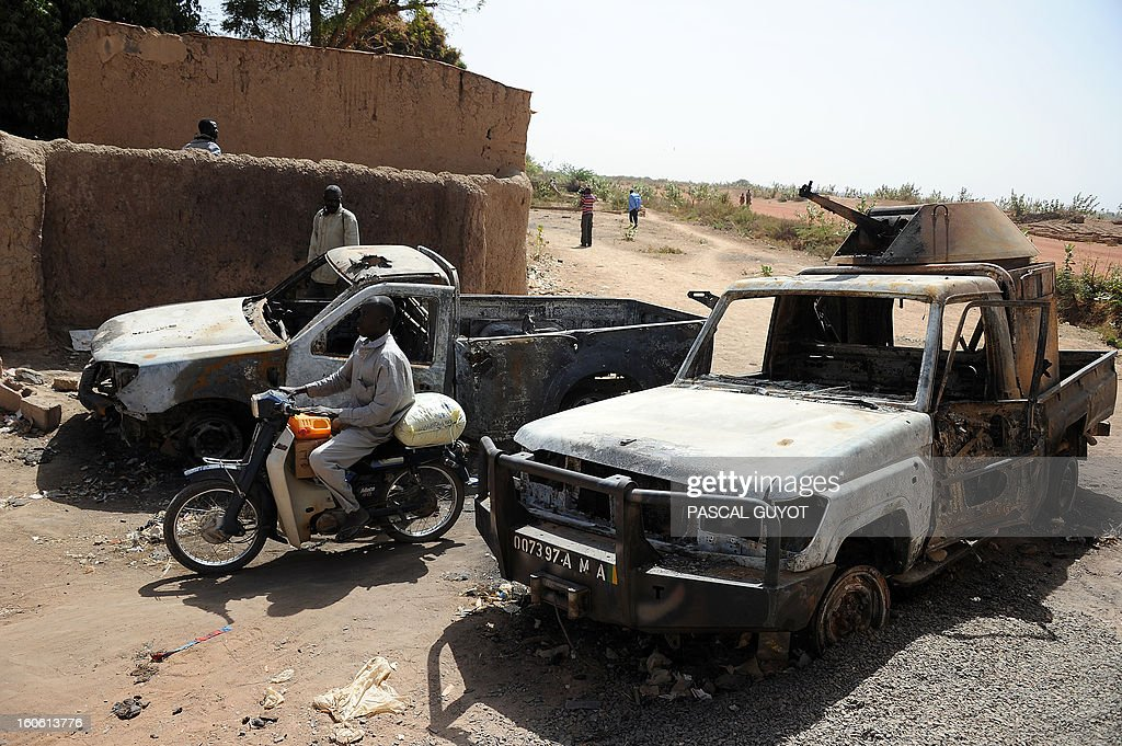 A man rides a bike past two burnt-out wrecks of vehicles allegedly used by Islamists following a major air strike, on February 3, 2013 in Diabaly. France said it carried out major air strikes on February 3, 2013 near Kidal, the last bastion of armed extremists chased from Mali's desert north in a lightning French-led offensive, after a whirlwind visit by President Francois Hollande. An army spokesman said 30 warplanes had bombed training and logistics centres run by Islamist extremists overnight in the Tessalit area north of Kidal, where French troops took the airport Wednesday and have been working to secure the town itself.