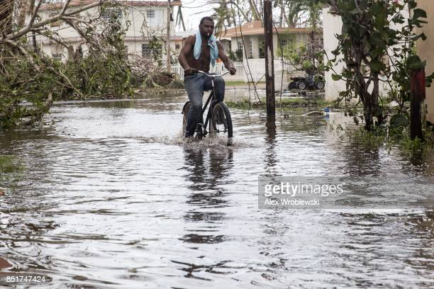 A man rides a bike through high water in Loiza Puerto Rico on September 22 2017 Many on the island have lost power running water and cell phone...
