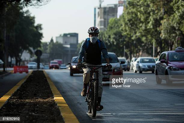 A man rides a bike wearing a mask on April 5 2016 in Mexico City Mexico According to authorities have declared a pollution alert after smog rose to...