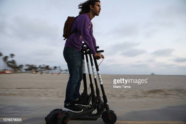 A man rides a Bird shared dockless electric scooter while transporting three others along Venice Beach on August 13 2018 in Los Angeles California...