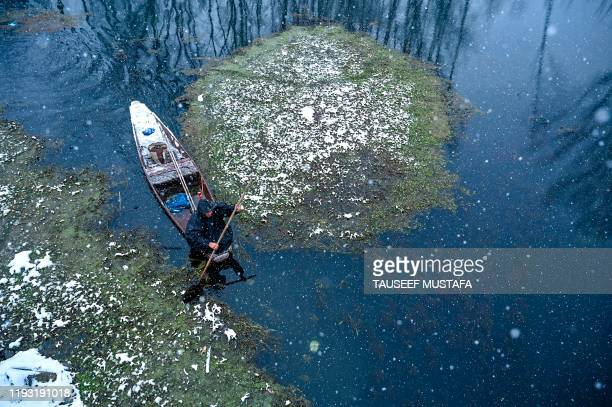 A man rides a boat in the Dal Lake during a snowfall in Srinagar on January 12 2020