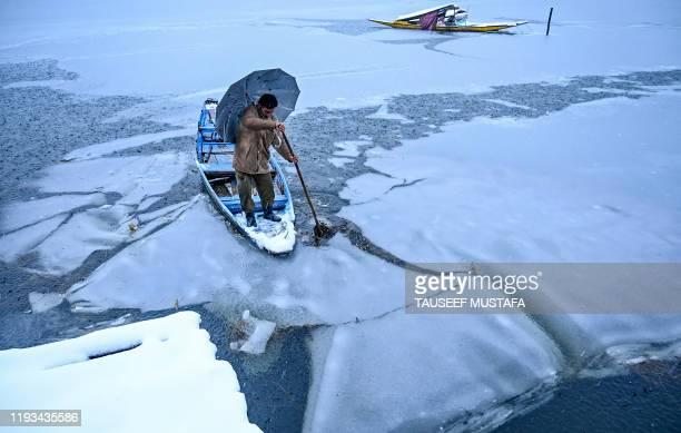 TOPSHOT A man rides a boat in the Dal Lake during a snowfall in Srinagar on January 13 2020