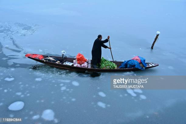 A man rides a boat loaded with vegetables near a frozen portion of Dal lake after a heavy snowfall in Srinagar on January 16 2020