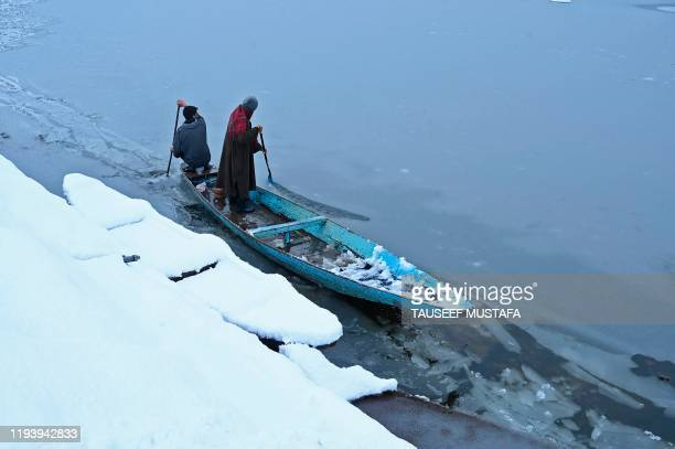 A man rides a boat near a frozen portion of Dal lake after a heavy snowfall in Srinagar on January 16 2020
