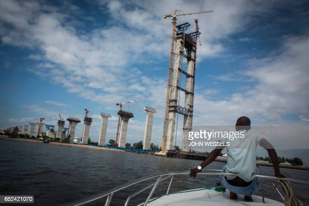 A man rides a boat near the Catembe side of the construction site of the MaputoCatembe Bridge which will be the longest suspension bridge in Africa...
