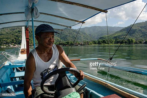 A man rides a boat on the Taal Lake a large fresh water lake near Manila