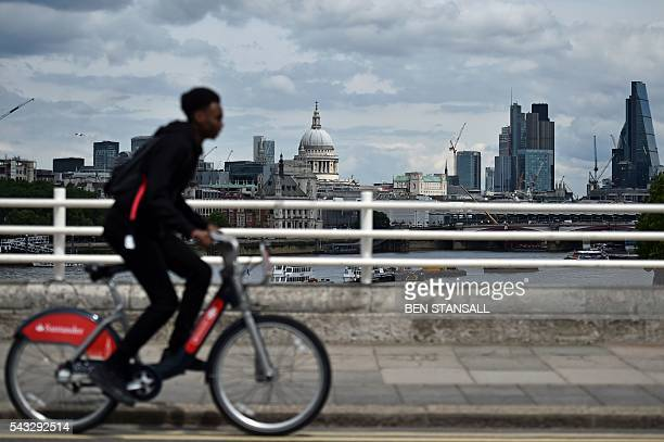 A man rides a 'Boris Bike' over Waterloo bridge with a backdrop of St Paul's Cathedral and buildings in City of London in central London on June 27...