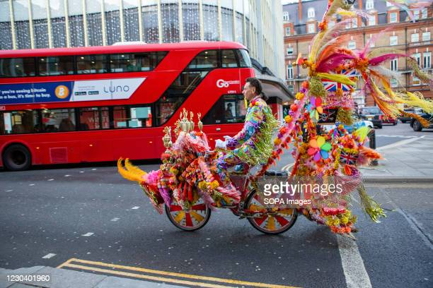 Man rides a brightly-coloured novelty bicycle at Sloane Square in London. The bike is decorated with flowers and colourful feathers.