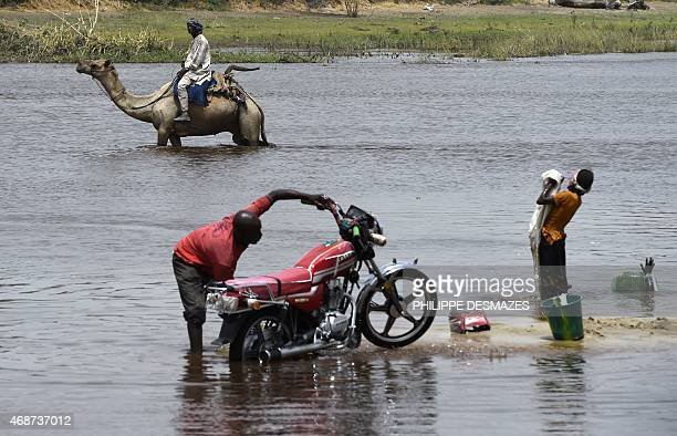 A man rides a camel as he crosses a branch of Lake Chad on April 6 2015 in N'Gouboua which was attacked by Islamist group Boko Haram on February 12...