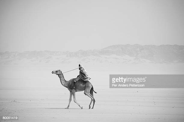 A man rides a camel in the desert near the border of Darfur close to the Oure Cassoni refugee camp on July 26 2007 about 23 kilometers outside Bahai...
