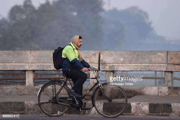 A man rides a cycle in the cold weather morning at Mayur Vihar extension on December 9 2017 in New Delhi India It was a cold morning in New Delhi on...