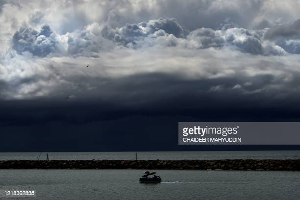 Man rides a duck pedal boat bike under dark clouds by the shores of Banda Aceh on June 8, 2020. - June 8 marks World Oceans Day.