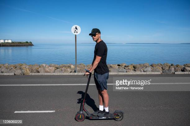 A man rides a electric scooter on Cardiff Bay barrage on the hottest day of the year on May 20 in Cardiff Wales The Met Office have said temperatures...