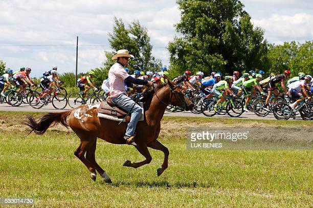 A man rides a horse as the peloton takes the start of the 13th stage of the 99th Giro d'Italia Tour of Italy from Palmanova and Cividale del Friuli...