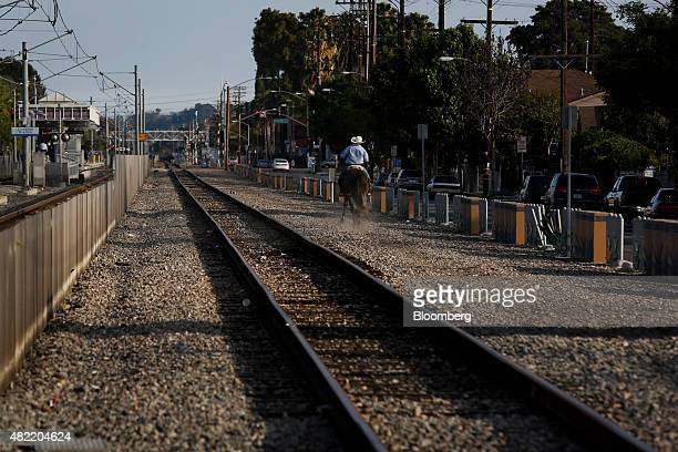 A man rides a horse next to the Metro Blue Line light rail tracks in Compton California US on Monday July 6 2015 It can be a letdown for LA Hood Life...